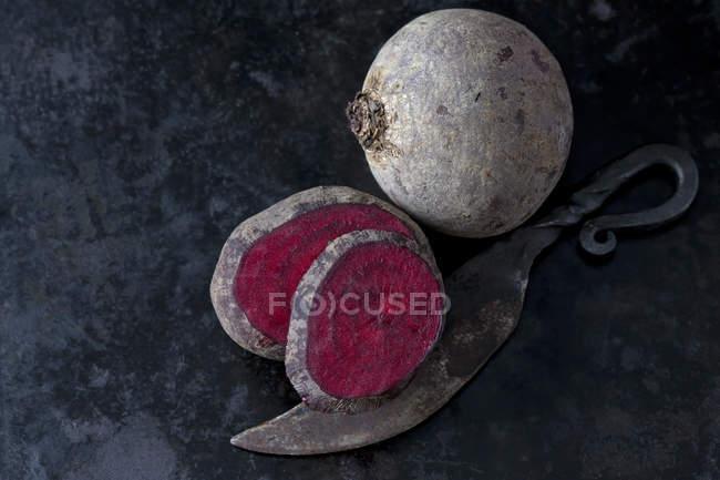 Ganze und geschnittene Rote Bete und ein altes Messer auf dunklem Metall — Stockfoto