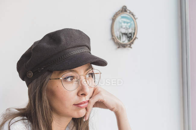 Stylish young woman wearing glasses and cap thinking — Stock Photo