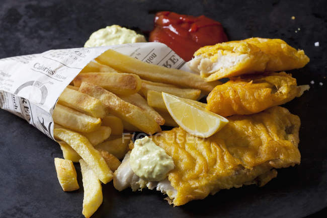 Fish and chips with remoulade, ketchup and lemon slice — Stock Photo