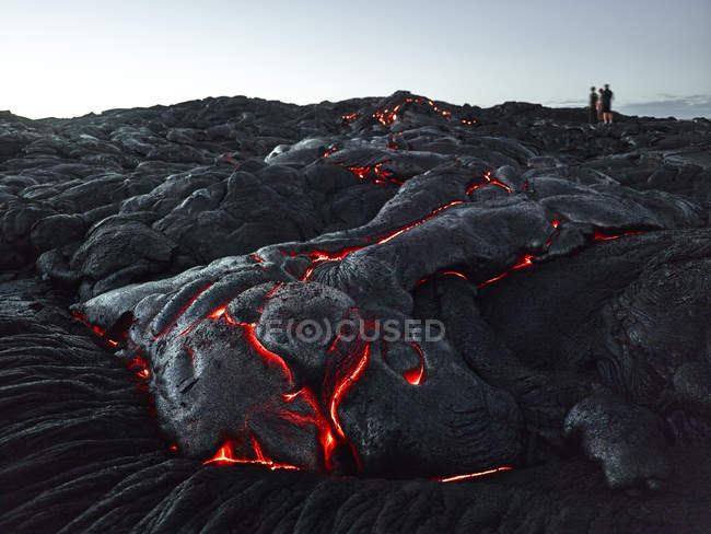 Hawaii, Big Island, Hawai'i Volcanoes National Park, tourists standing on lava field — Stock Photo