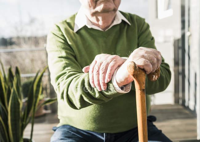 Homme aîné s'asseyant à la fenêtre et s'appuyant sur la canne — Photo de stock