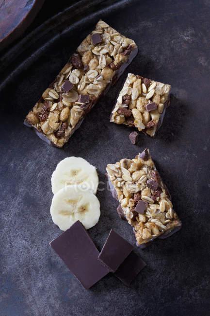 Muesli bars with oat flakes, banana and chocolate on dark metal background — Stock Photo