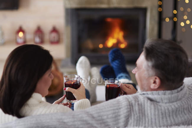 Pareja madura con bebidas calientes en la sala de estar en la chimenea - foto de stock