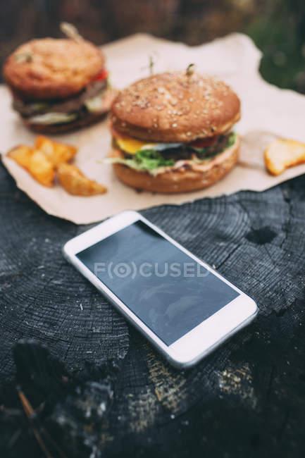 Hamburguesas y smartphone con sello - foto de stock