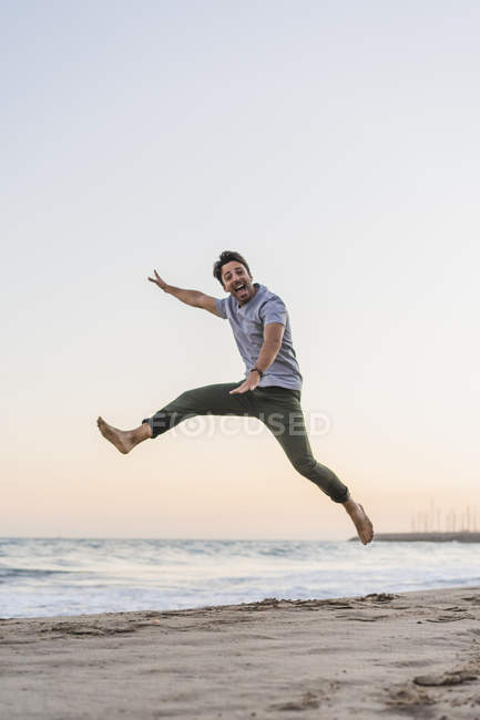 Happy young man jumping in the air on the beach at sunset — Stock Photo