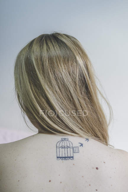 Back view of blond woman with tattoo on her neck — Stock Photo