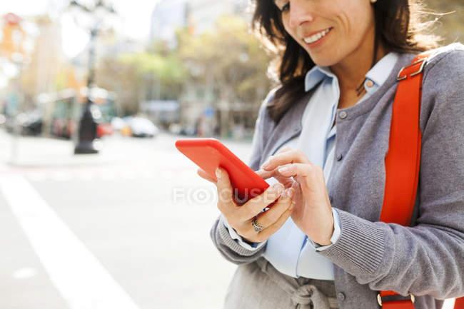 Крупный план женщины с мобильного телефона в городе — стоковое фото