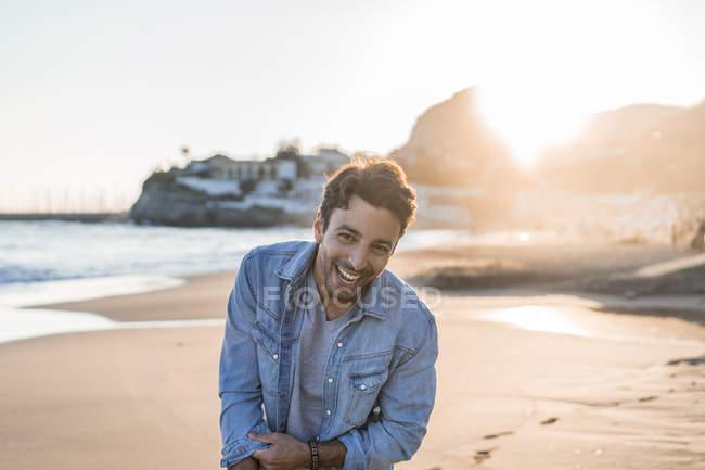 Retrato de um jovem rindo na praia ao pôr do sol — Fotografia de Stock