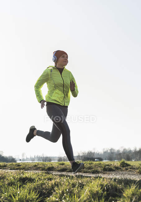 Young woman with headphones running on rural path — Stock Photo