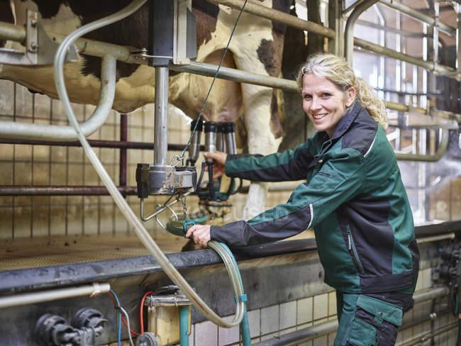 Портрет усміхнений жіночий фермер в стабільній доїння корова — стокове фото