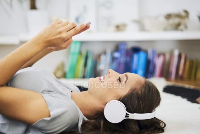 Улыбающаяся молодая женщина лежит на полу с наушниками и сотовым телефоном — стоковое фото
