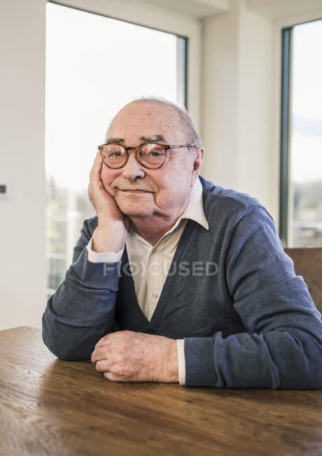 Verticale d'homme aîné s'asseyant à la table — Photo de stock