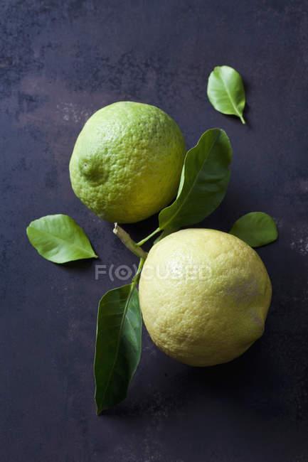 Frische reife und unreife Zitrone mit Blättern auf schwarzer Oberfläche — Stockfoto
