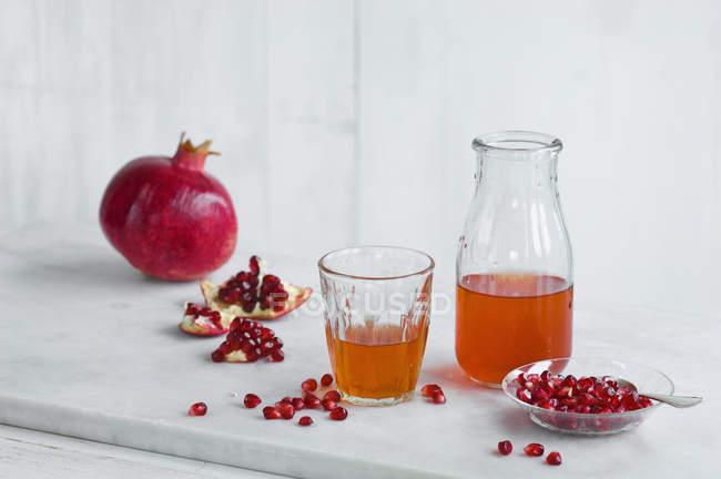Скляні та пляшки гранатового соку і цілого граната і гранатового насіння — стокове фото