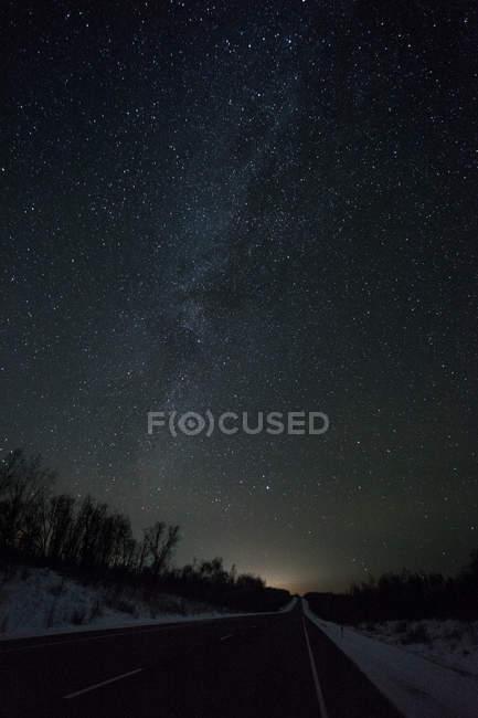 Russie, oblast d'Amour, route de campagne vide sous le ciel étoilé en hiver — Photo de stock
