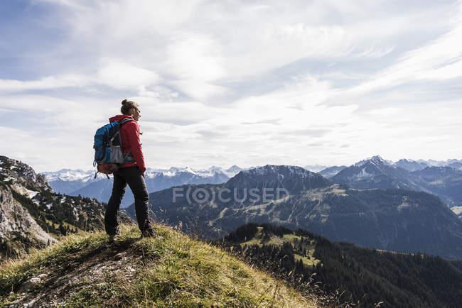 Autriche, Tyrol, jeune femme restant dans le paysage de montagne et regardant la vue — Photo de stock
