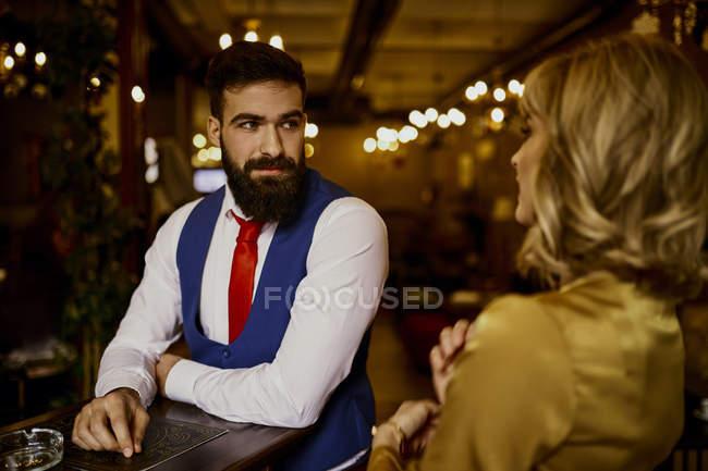 Modischer junger Mann sieht Frau in Bar an — Stockfoto