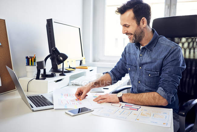 Smiling web designer working on draft at desk in office — Stock Photo