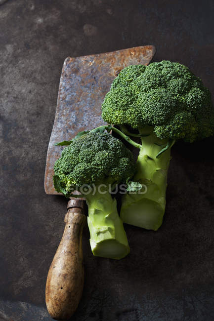 Broccoli and old rusty cleaver on dark grunge background — Stock Photo