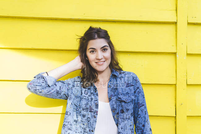Portrait of smiling young woman in front of yellow wooden wall — Stock Photo