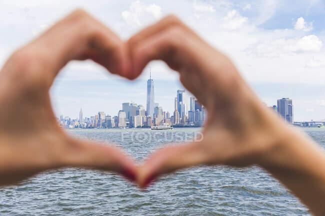 Estados Unidos, Nueva York, manos en forma de corazón frente al horizonte de Manhattan - foto de stock