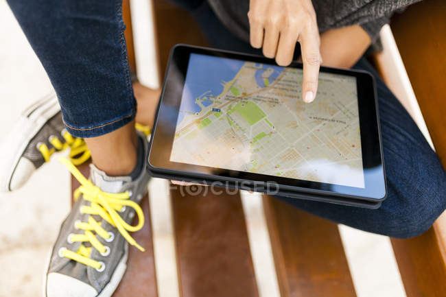 Close-up of woman using tablet with digital street map — Stock Photo