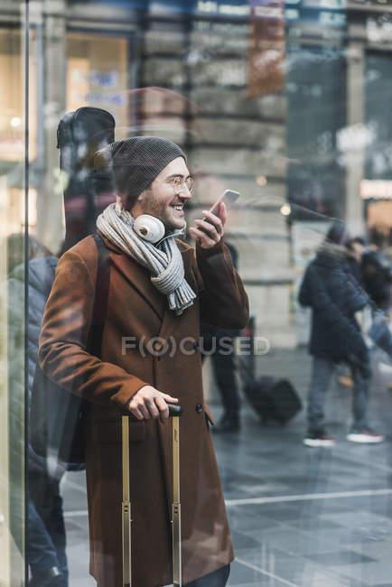 Улыбающийся молодой человек с футляром для гитары на станции с помощью мобильного телефона — стоковое фото