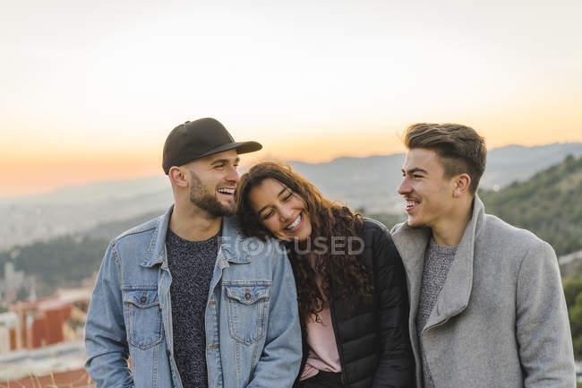 Ritratto di tre amici felici su una collina al tramonto — Foto stock