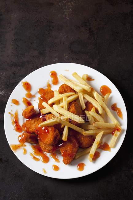 Teller mit Chicken Nuggets mit süßer Chilisoße und Pommes auf dunklem Metall — Stockfoto