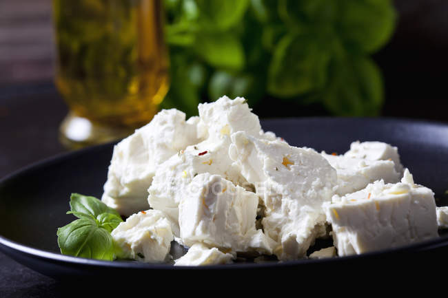 Feta, herbes and basil leaves on black plate, close-up — Stock Photo
