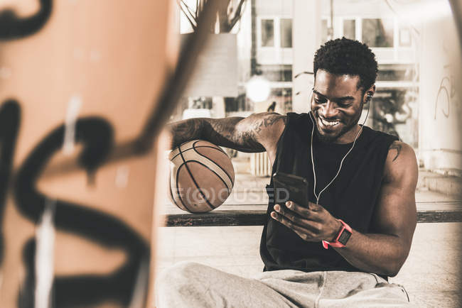 Smiling african american man with tattoos and basketball ball using smartphone and earphones — Stock Photo