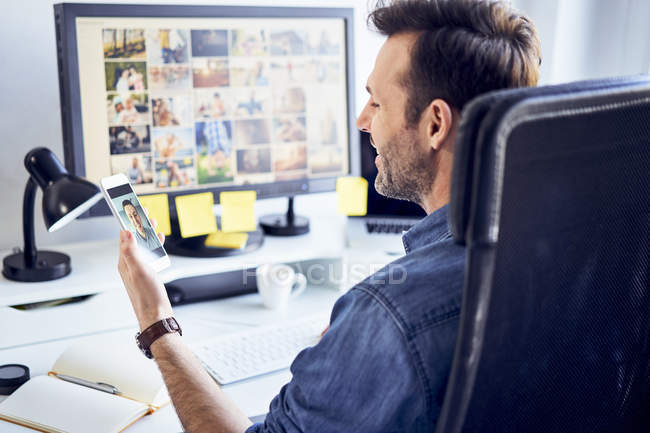 Photo editor at desk in office having video chat on his phone — Stock Photo