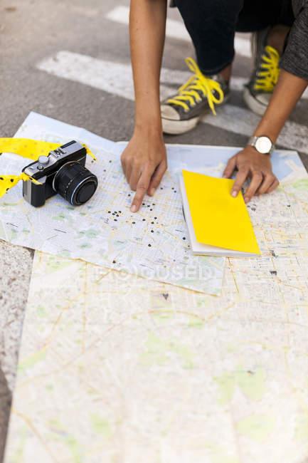 Крупный план женщины с камерой поиска на карте города — стоковое фото