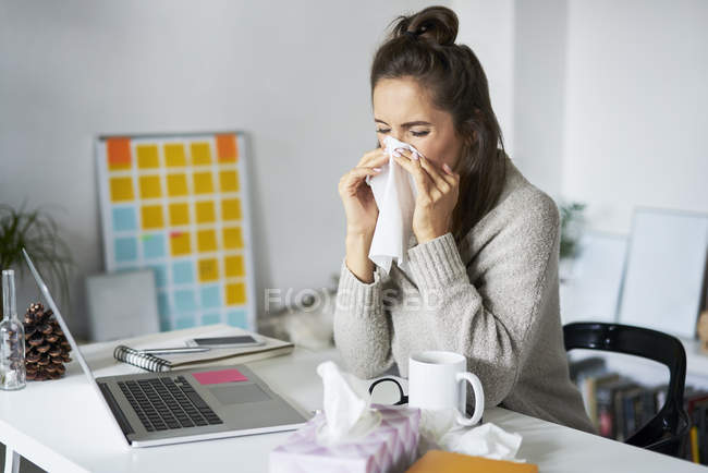 Ill woman at home at desk blowing her nose — Stock Photo
