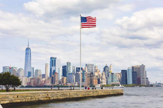 EUA, Nova York, vista panorâmica de Manhattan com bandeira americana em primeiro plano — Fotografia de Stock