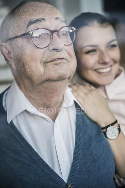 Verticale de jeune femme de sourire avec l'homme aîné à la fenêtre — Photo de stock