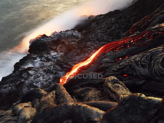 Hawaii, Big Island, Hawai'i Volcanoes National Park, lava flowing into pacfic ocean — Stock Photo