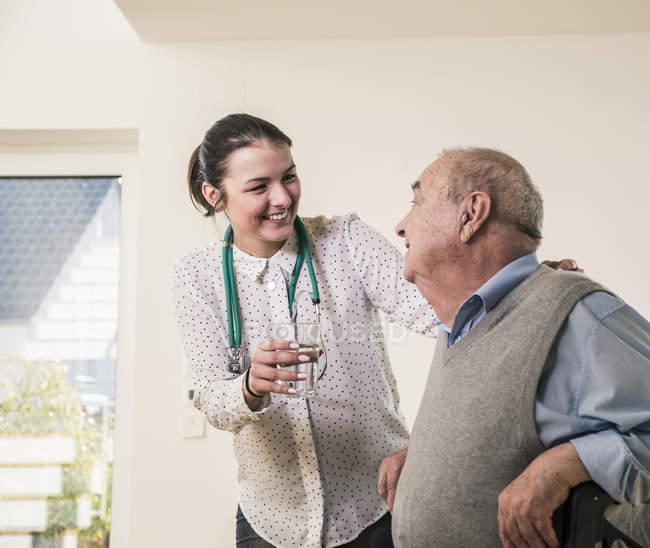 Homme aîné souriant à l'infirmière retenant le verre de l'eau à la maison — Photo de stock