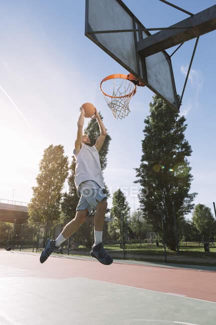 Мужчина играет в баскетбол на баскетбольной площадке — стоковое фото
