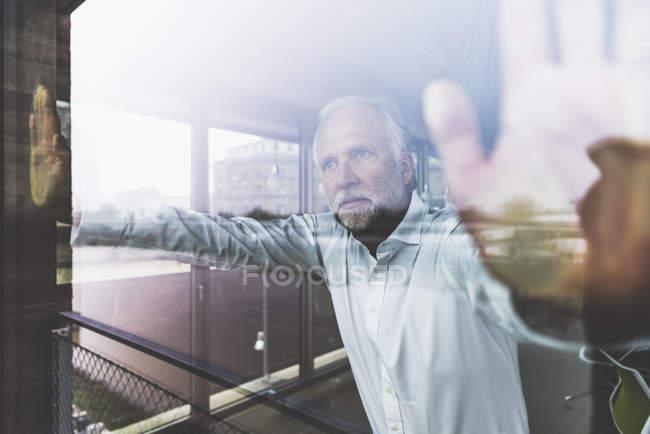 Ernsthafter reifer Geschäftsmann steht am Fenster und schaut hinaus — Stockfoto