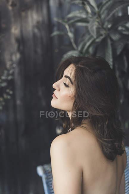 Vista lateral da mulher jovem com cabelo castanho e ombro nu — Fotografia de Stock
