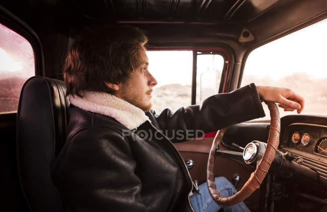 USA, California, Joshua Tree, young man sitting in an pick-up truck — Stock Photo