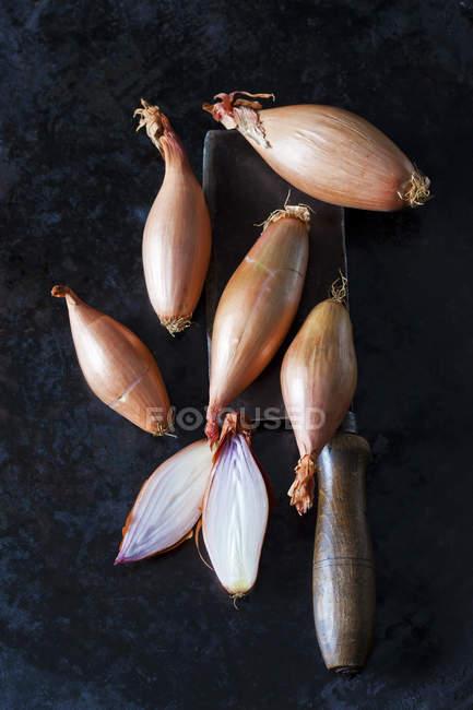 Chalotas cortados e inteiros da banana e um cutelo velho — Fotografia de Stock