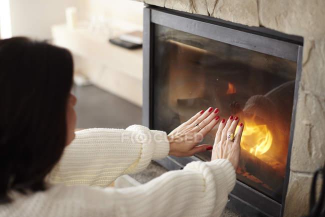Пожилая женщина согревает руки у камина — стоковое фото