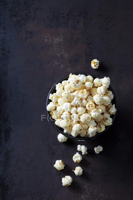 Nahaufnahme von Schüssel Popcorn auf rostigem Hintergrund — Stockfoto