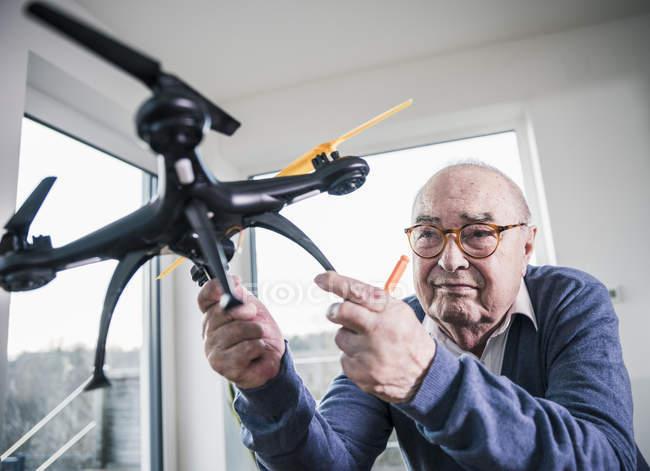 Verticale d'homme aîné retenant un drone — Photo de stock
