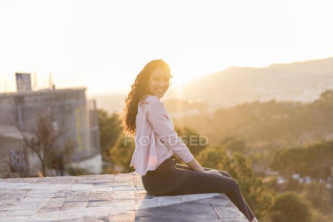 Счастливая молодая женщина с длинными волосами сидит на стене на закате — стоковое фото