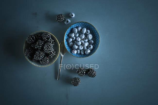 Tazón de arándanos frescos y moras sobre fondo azul oscuro - foto de stock