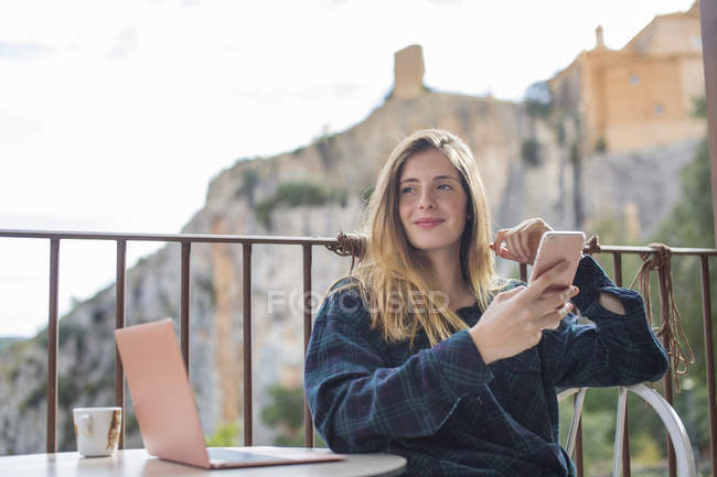 Spain, Alquezar, portrait of relaxed young woman with laptop and cell phone, sitting on terrace — Stock Photo