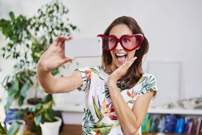 Felice giovane donna in occhiali a forma di cuore prendendo selfie — Foto stock